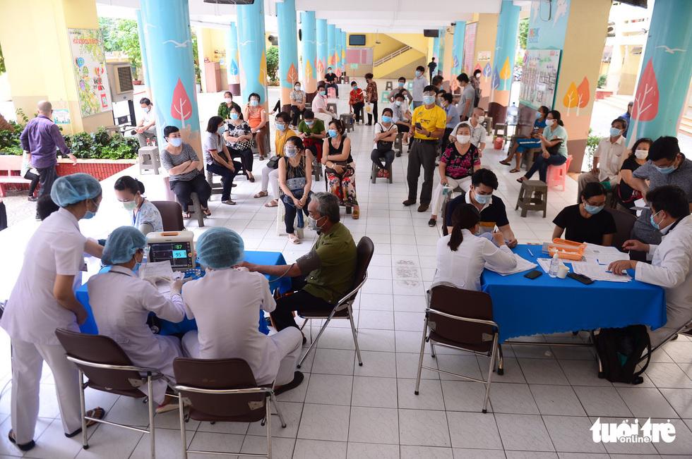 Người dân TP.HCM đi tiêm vắc xin ngừa COVID-19 - ảnh 1
