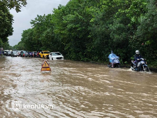 Ảnh: Mưa lớn kéo dài do ảnh hưởng của bão số 7, nhiều nơi ở Hà Nội ngập sâu, người dân chật vật di chuyển - ảnh 8