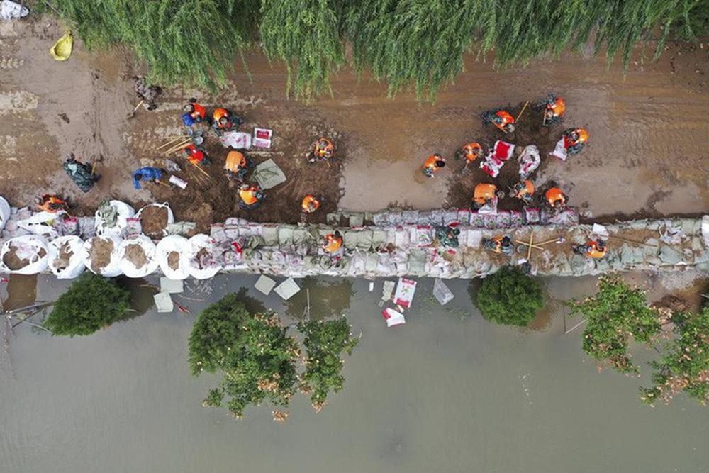 Trung Quốc: Đang chạy, xe buýt bị lũ đẩy xuống sông - ảnh 2