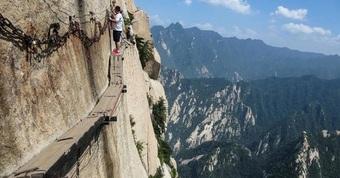 Du khách liều mình đi bộ trên tấm ván nhỏ ven ngọn núi cao hơn 2000 m